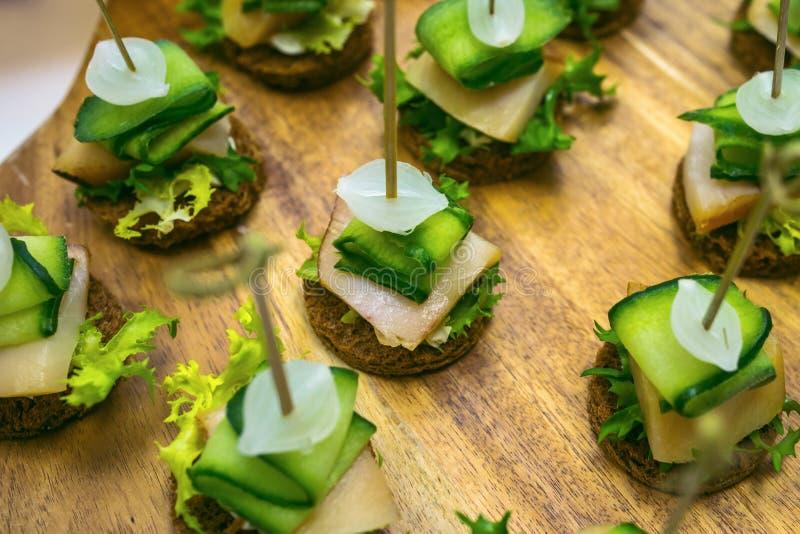 Canape med rimmat späcker, löken, gurkan, rågbröd och persilja Sköta om banketttabellen med olika matmellanmål fotografering för bildbyråer