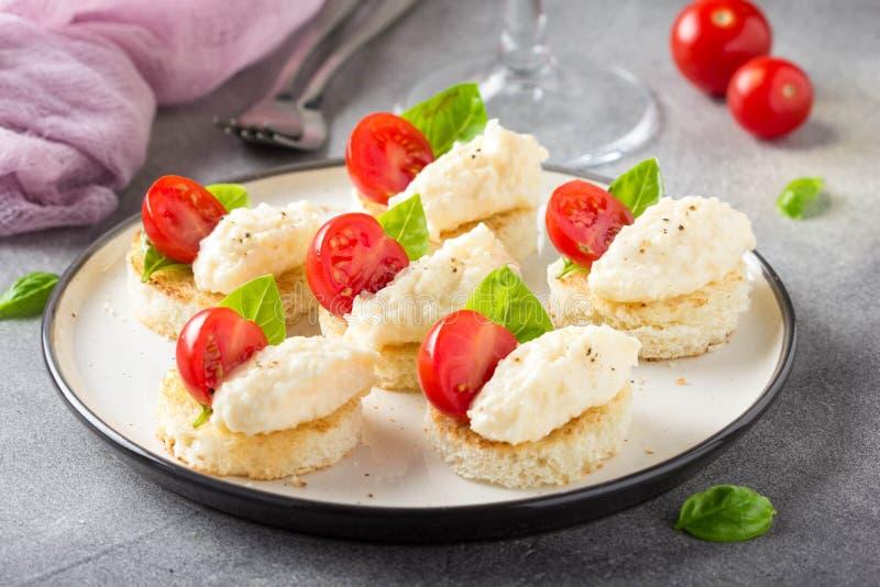 Canape met kaasmousse, kersentomaat en basilicum, kleine sandwich op knapperige toost met kaas en knoflookbollen heerlijk stock afbeelding