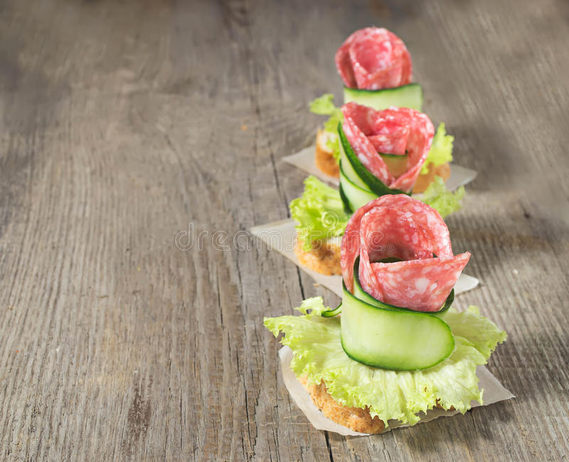 Canape mit Salami, Gurke und Salat auf Holztisch lizenzfreie stockfotografie