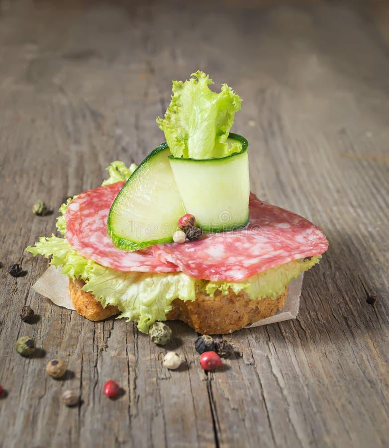 Canape mit Salami, Gurke und Salat auf Holztisch stockfoto