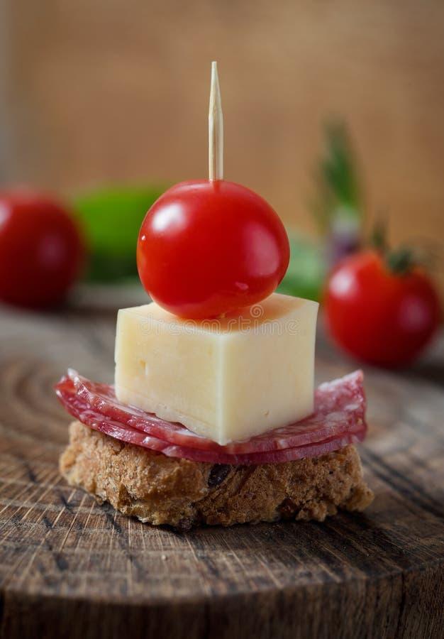 Canape mit Salami-, Käse- und Kirschtomate auf hölzernem Hintergrund stockbild