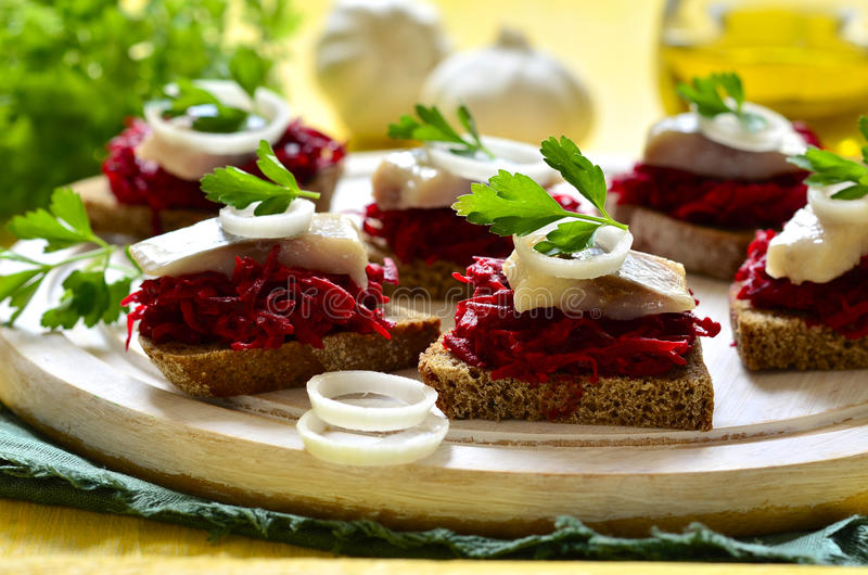 Canape from rye bread with herring slice and beetroot. stock photo