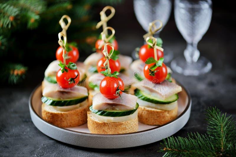 Canape z solonym ?ledziem, og?rkiem, gotowanymi grulami i czere?niowym pomidorem na ?yt croutons, abstrakcjonistycznych gwiazdk?  zdjęcia stock