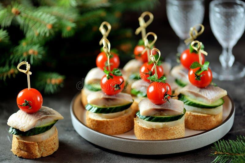 Canape z solonym ?ledziem, og?rkiem, gotowanymi grulami i czere?niowym pomidorem na ?yt croutons, abstrakcjonistycznych gwiazdk?  zdjęcia royalty free