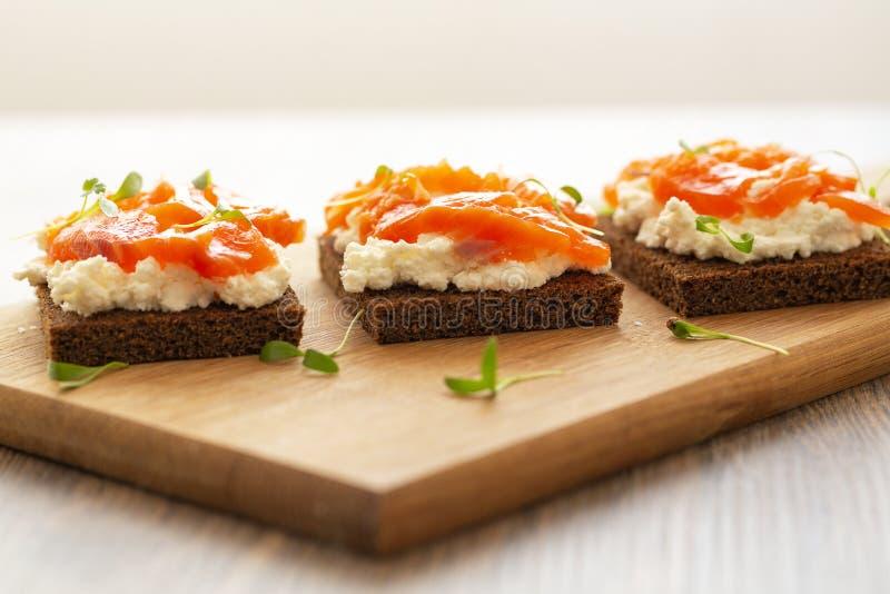 Canape z uwędzonym łososiem i kremowym serem na drewnianej desce Selekcyjna ostro?? obrazy royalty free