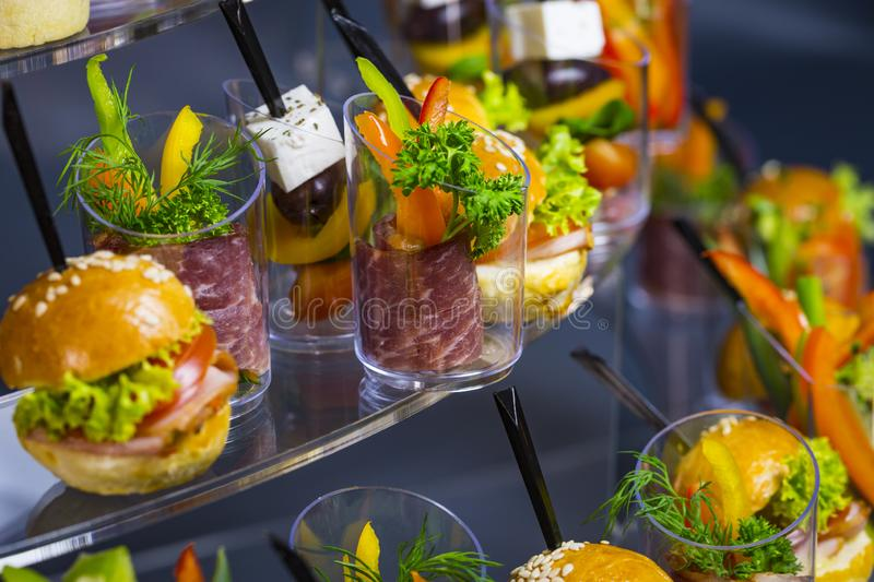Canapes with cheese salads meat and seafood in plastic cups. stock photos