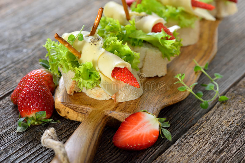 Canapes with cheese and strawberries royalty free stock photography