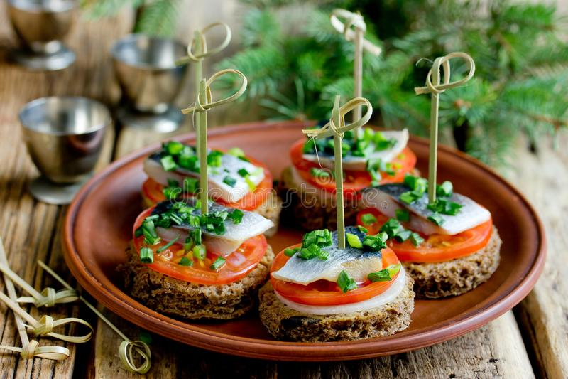 Canapes com pão de centeio, faixa de arenques salgada, mostarda, cebola, tomate fotos de stock