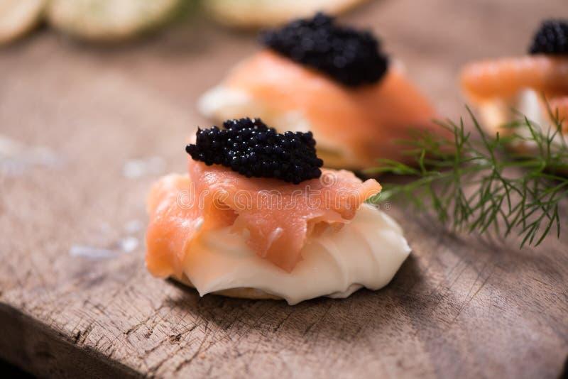 Canapes com salmões e o caviar fumados imagens de stock
