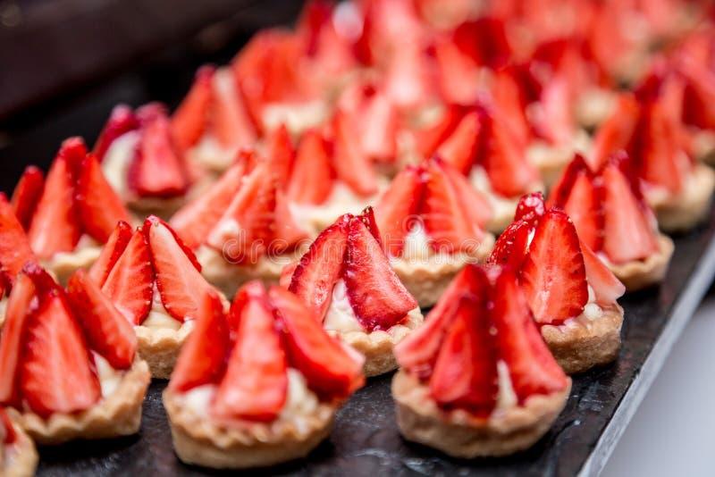 Canapes com a sobremesa da morango na tabela de banquete foto de stock royalty free