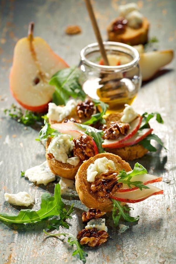 Canapes con queso verde, la pera fresca, la miel, las nueces caramelizadas y el arugula imagenes de archivo