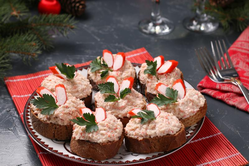 Canapes with cream cheese, crab sticks and beans on the dark background. Holiday snack stock photography