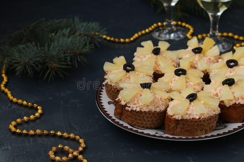 Canapes with cream cheese, crab sticks, black olives and pineapples. Christmas background, Copy space, horizontal stock images