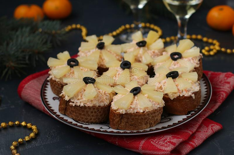Canapes with cream cheese, crab sticks, black olives and pineapples. Christmas background, horizontal royalty free stock photography