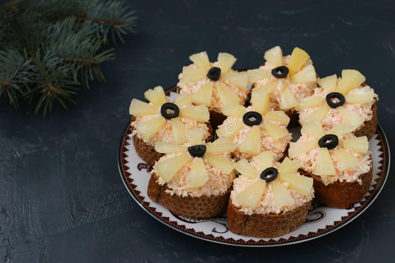 Canapes with cream cheese, crab sticks, black olives and pineapples. Christmas background, horizontal royalty free stock photos