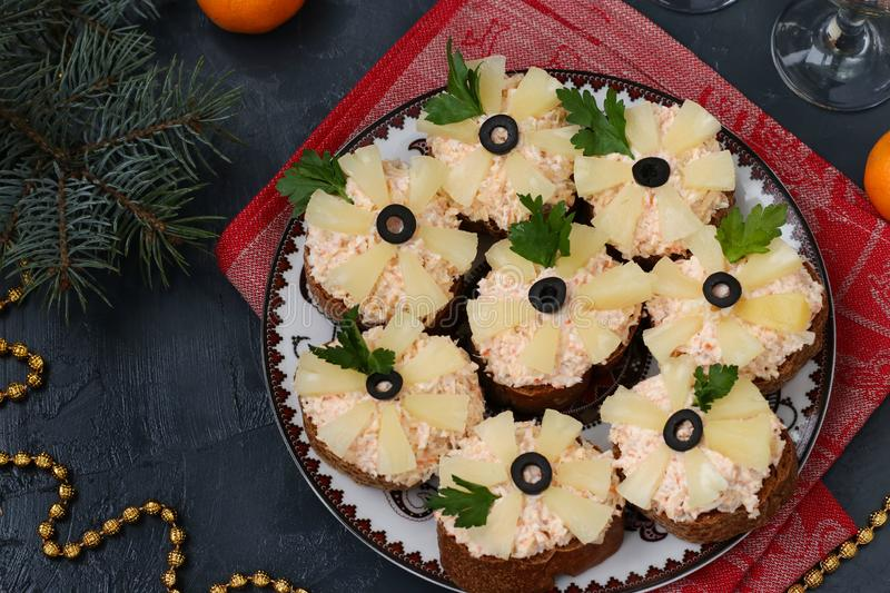 Canapes with cream cheese, crab sticks, black olives and pineapples. Christmas background, horizontal, top view stock images