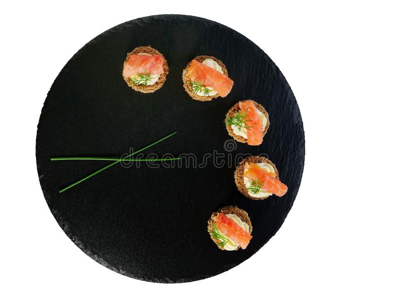 Canapes del salmón ahumado con la crema y el eneldo del queso servidos en el disco negro de la pizarra fotos de archivo libres de regalías