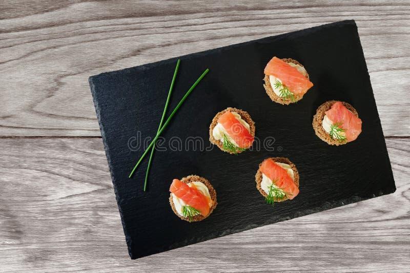 Canapes del salmón ahumado con la crema y el eneldo del queso servidos en el disco negro de la pizarra imagen de archivo