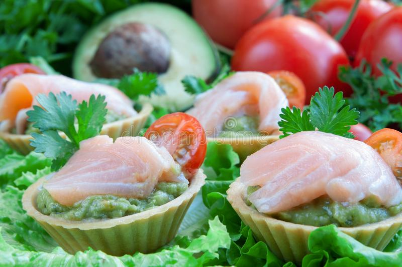Canapes with guacomole and salmon on a vegetable background stock photo