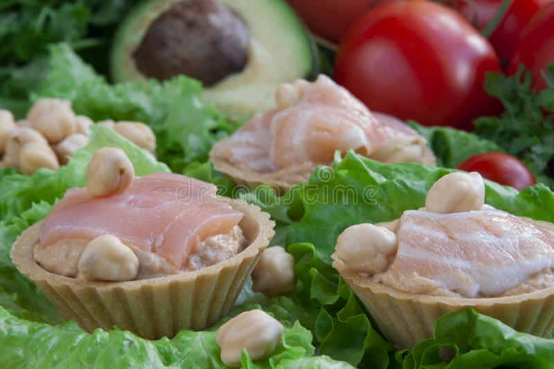 Canapes with hummus and salmon on a vegetable background royalty free stock photos