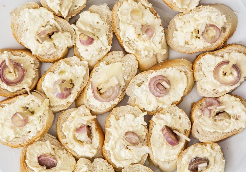 Canapes sabrosos con la mantequilla y la cebolla, tema del aperitivo fotografía de archivo