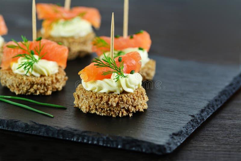 Canapes saumonés fumés avec de la crème et l'aneth de fromage sur le pain brun images stock