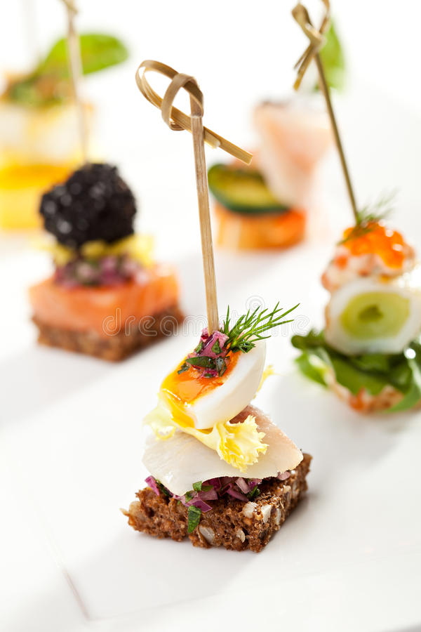 Canapes. Seafood and Vegetables Canapes on White Dish stock image