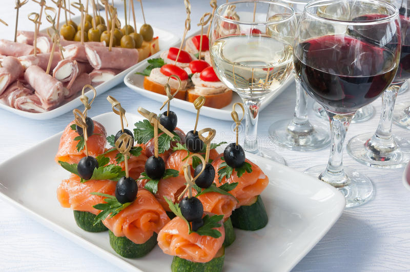 Canapes on the white plates. Mini canapes on white plates in daylight royalty free stock photography