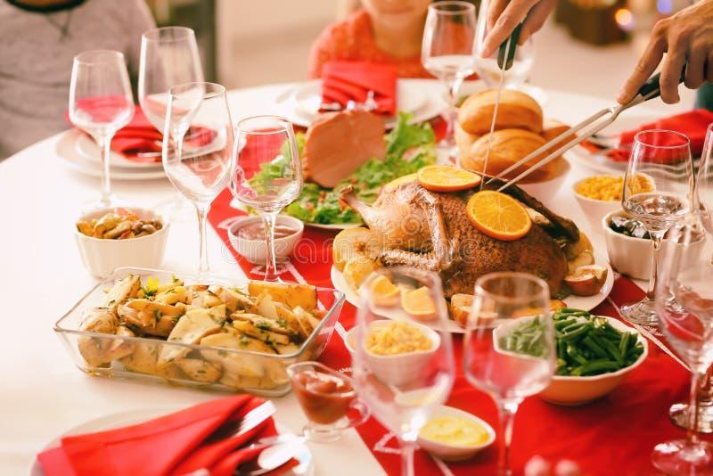 Canard rôti savoureux de coupe d'homme avec des oranges pendant le dîner de Noël photos stock