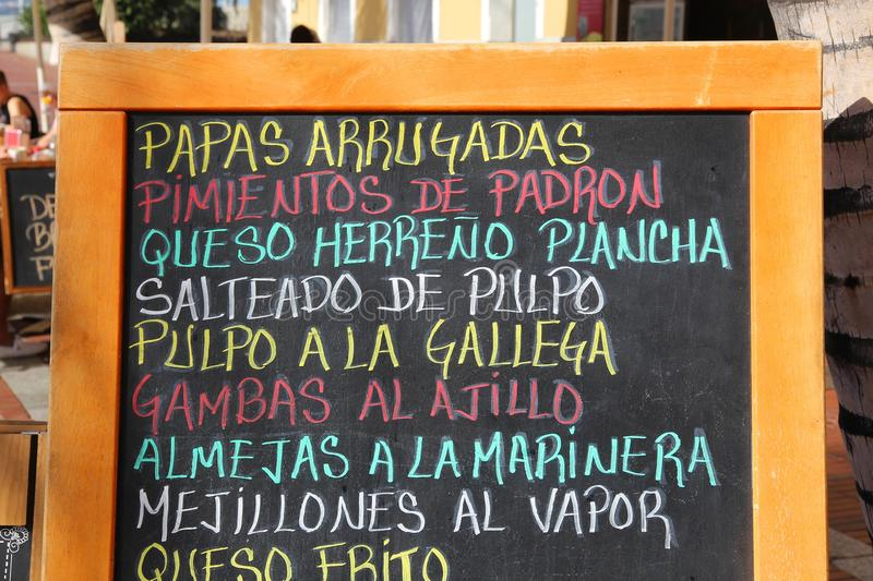 Canary Islands cuisine. Menu sign with papas arrugadas (wrinkly potatos), pimientos (peppers), queso (cheese), sauteed octopus, shrimps, clams and mussels stock photography