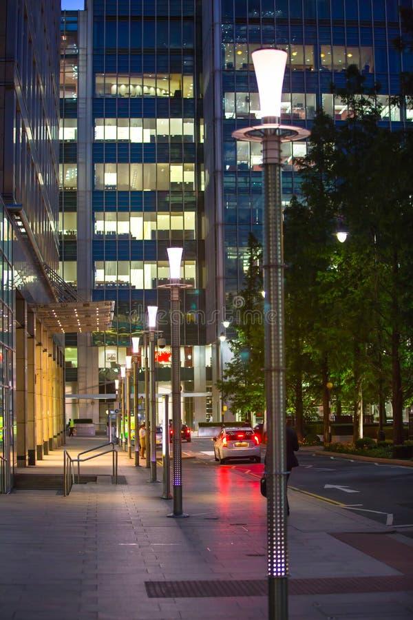 Canary Wharf, άποψη οδών νύχτας με τους φωτεινούς σηματοδότες και τα αυτοκίνητα στοκ φωτογραφία