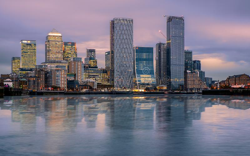 Canary wharf cityscape. The buildings are reflected in Thames river's water. stock images