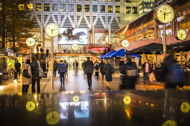 Canary Wharf financial district, London. Business people walking in Canary Wharf by the iconic clock installation, London`s financial district royalty free stock photos