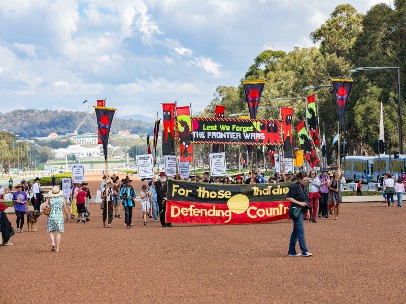 """CANBERRA, AUSTRALIA †""""Kwiecień 25, 2019: Kontyngent Tubylczy ludzie maszeruje przy Anzac dnia Krajową ceremonią trzymającą doro obrazy royalty free"""