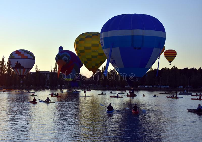 Kayakers watching big colourful hot air balloons. Canberra, Australia - March 11, 2018. Kayakers watching big colourful hot air balloons at Lake Burley Griffin royalty free stock image