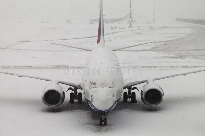 Cancelled Flight. A commercial plane is covered with snow royalty free stock photo