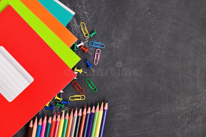 Cancelleria luminosa sui taccuini neri, sulle matite, sulle forbici e su altre di un fondo del bordo fotografia stock libera da diritti