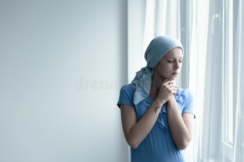 Cancer survivor deep in thought. Standing by the window royalty free stock images