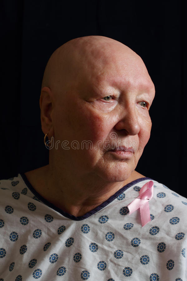 Cancer Survivor. A dramatic portrait of an older bald woman who is missing all her hair from a battle with cancer wearing a pink ribbon on her hospital gown royalty free stock photography