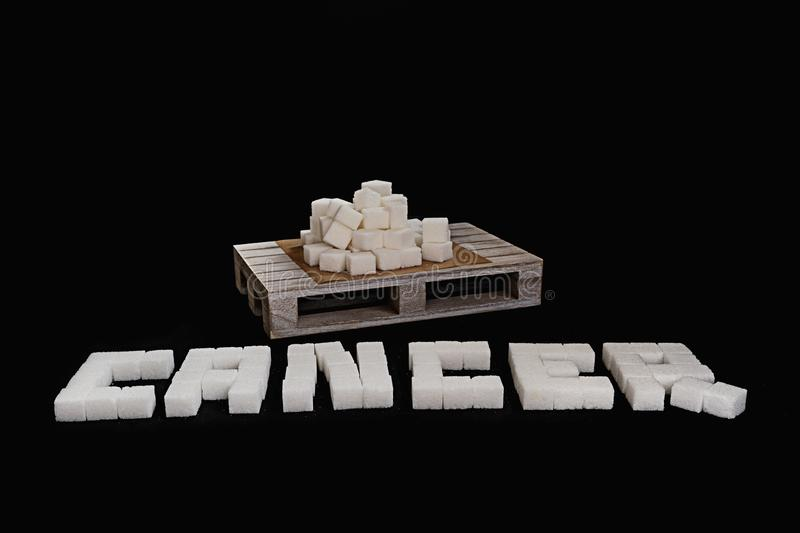Cancer text written with white refined sugar cubes. Suggesting dieting concept. No sugar concept suggesting no sugar consumption to improve health stock image