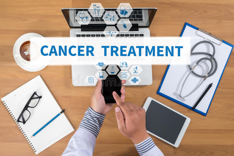 CANCER TREATMENT. Doctor working at office desk and using a mobile touch screen phone, computer and medical equipment all around, top view, coffee stock images