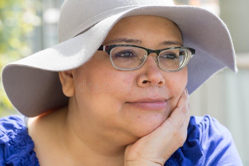 Cancerpatienten bär hatten för solskydd arkivbild