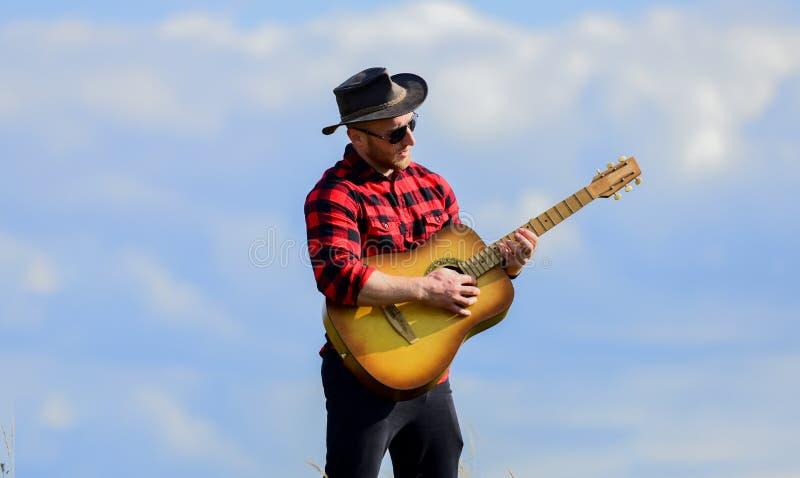Canción de senderismo Hombre guapo con guitarra Estilo de campo Vacaciones de verano Jugar a la hermosa melodía Concepto de músic fotos de archivo libres de regalías