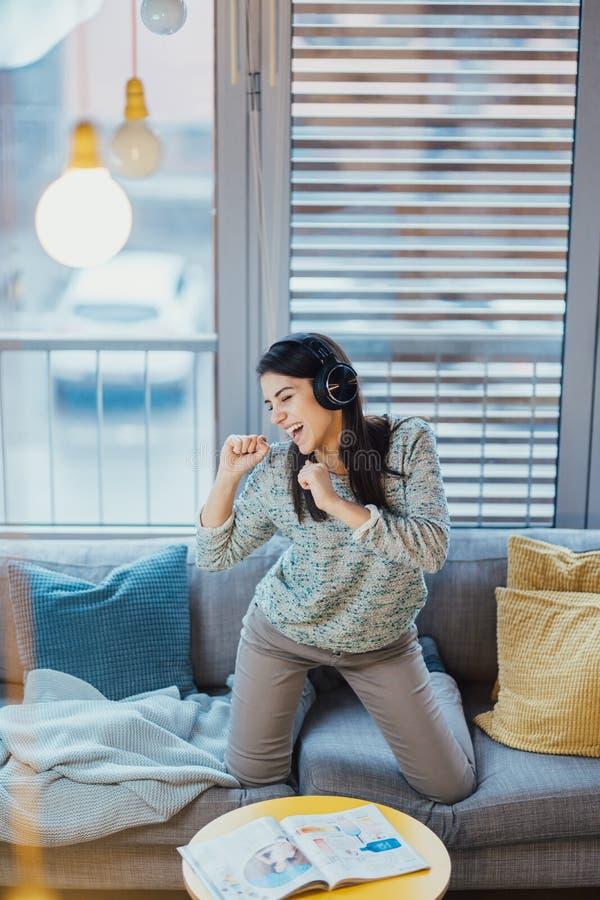 Canción del canto con la emoción Capacidades vocales practicantes Mejora de la gama Mujer alegre que escucha la música con los au imágenes de archivo libres de regalías