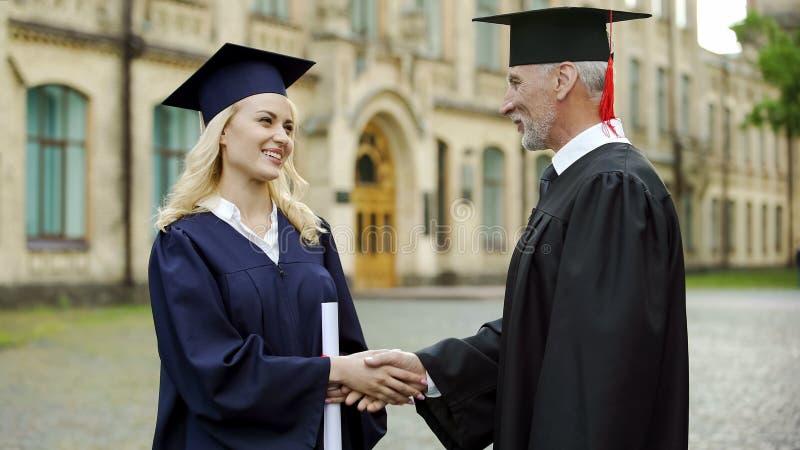 Canciller de la universidad que da el diploma al estudiante, felicitando y sacudiendo la mano imágenes de archivo libres de regalías