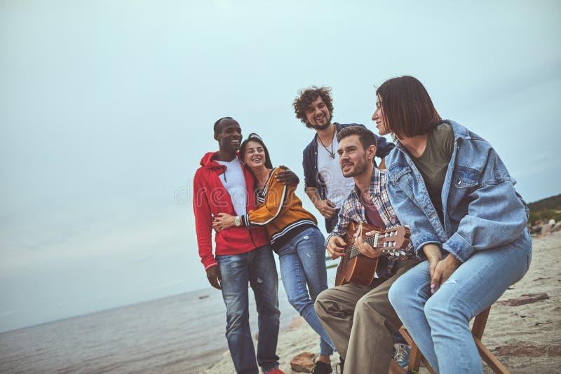 Canciones del canto del individuo de la sonrisa debajo de la guitarra imagen de archivo libre de regalías