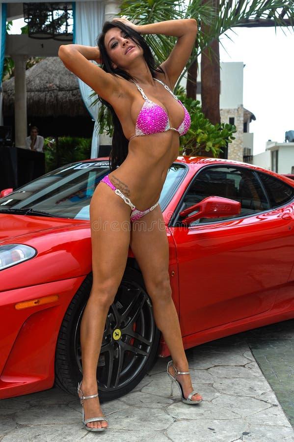 CANCUN MEXICO - MAJ 03: Modellen Morgan Maria poserar yttersidan med den röda bilen under halv-finaler IBMS 2014 royaltyfri foto