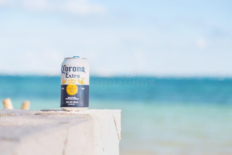 CANCUN, QR, МЕКСИКА - 4-ОЕ ФЕВРАЛЯ 2019: Конец-вверх консервной банки традиционного мексиканского пива короны с пляжем с белым пе стоковые фото