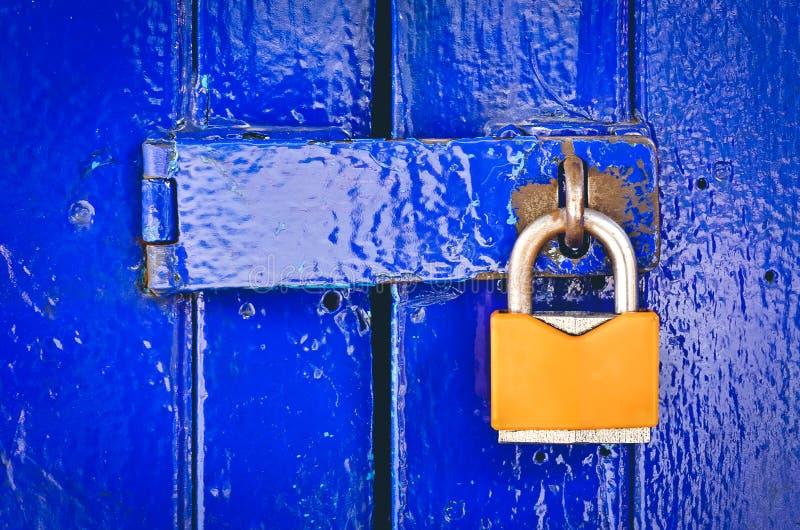 Candado anaranjado viejo en la puerta azul de madera fotos de archivo libres de regalías