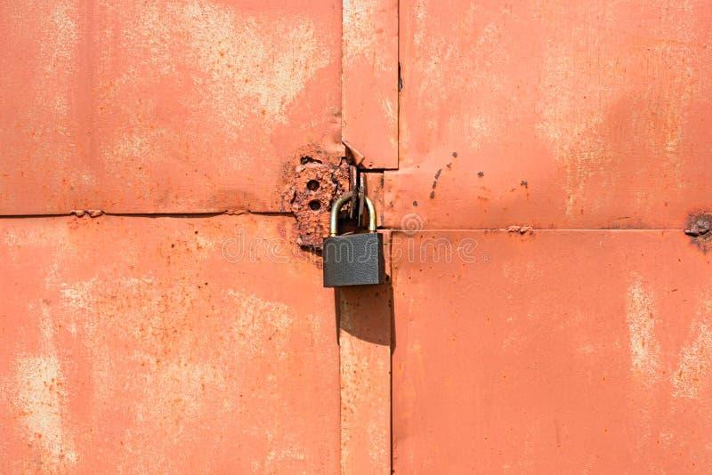 Candado en una puerta anaranjada vieja del garaje fotografía de archivo